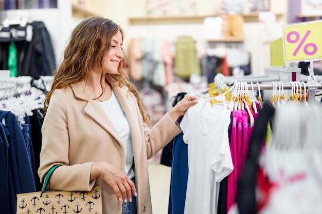 Vrij elegante vrouw die in klerenopslag winkelt. meisje kiezen, kijken en winkelen trendy kleding.