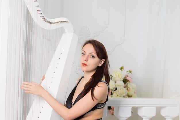 Vrij elegante vrouwelijke muzikant in zwarte avondkleding zittend op de harp spelend met haar vingers over de snaren terwijl ze naar de camera kijkt