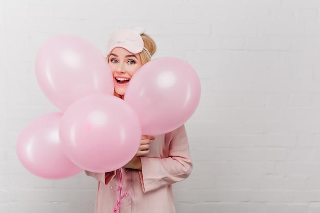 Vrij emotioneel meisje dat in pyjama partijballons in ochtend houdt. opgewonden blonde vrouw die iets viert, lachend op witte muur.