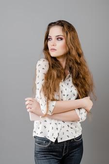 Vrij emotionele vrouwen weraing overhemd en jeans die over grijze muur wordt geïsoleerd
