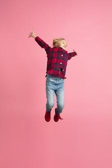 Vrij en gelukkig, vliegend, hoog springend. portret van het blanke meisje op roze muur. mooi model met blond haar.