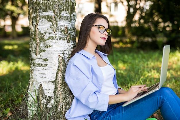 Vrij ernstig meisje in blauwe jeans werkt met laptop in stadspark