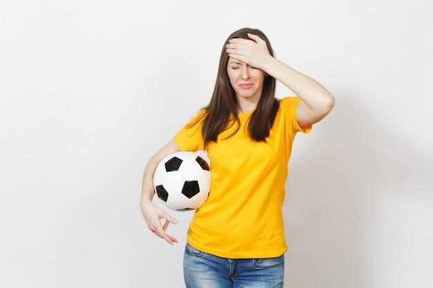Vrij europese jonge trieste overstuur vrouw, voetbalfan of speler in geel uniform houdt voetbal, maakt zich zorgen over het verliezen van team geïsoleerd op een witte achtergrond. sport, voetbal, lifestyle concept.