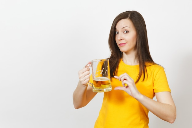 Vrij europese jonge verdrietig overstuur vrouw, voetbalfan of speler in geel uniform houdt pint mok bier, maakt zich zorgen over het verliezen van team geïsoleerd op een witte achtergrond. sport, voetbal, lifestyle concept.