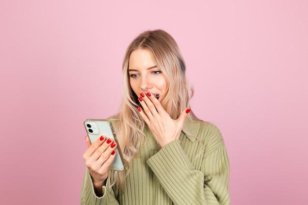 Vrij europese vrouw in casual gebreide trui op roze muur Gratis Foto