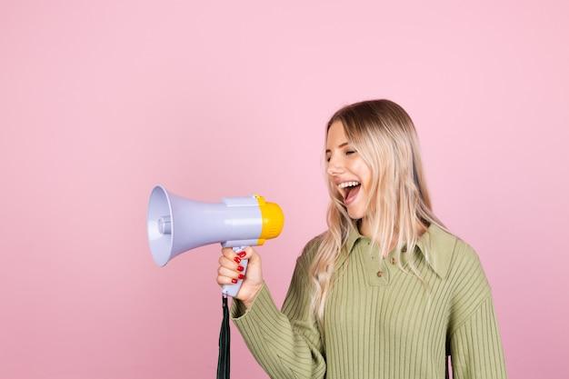 Vrij europese vrouw in casual sweater met megafoon op roze muur