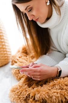Vrij europese vrouw in casual witte trui ligt op de vloer thuis door raam met telefoon, positief chatten, een gesprek voeren, sms-bericht verzenden