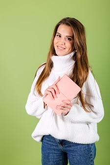 Vrij europese vrouw in toevallige witte geïsoleerde sweater, leuke positieve holdingskladblok