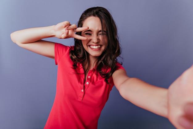 Vrij europese vrouw lachen terwijl poseren met vredesteken. modieus bruinharige meisje selfie maken op paarse muur.