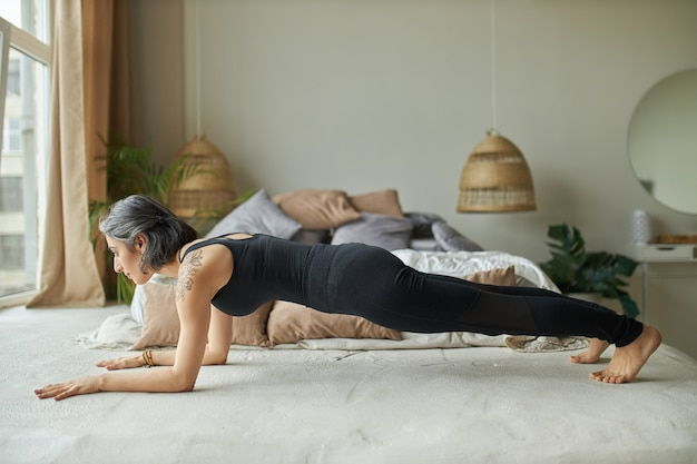 Vrij fit meisje in zwarte sportkleding die zich in elleboogplank bevindt, kernspieren uitwerkt, buik en ruggengraat versterken
