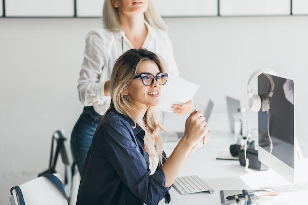 Vrij freelancer meisje zit in de buurt van computer met zwart scherm en wegkijken met een glimlach