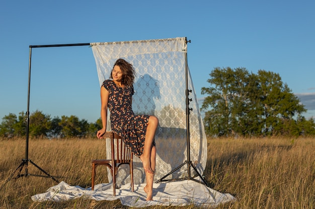 Vrij frisse jonge vrouw zittend op een stoel buiten in het veld en het dragen van in jurk op de achtergrond een rek met witte gordijnen. concept van zomervakantie in dorp en live stijl