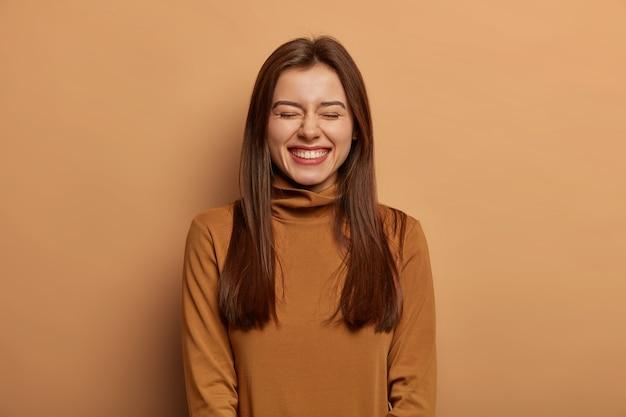 Vrij geamuseerde vrouw heeft lang donker steil haar, lacht van vreugde, draagt een bruine trui met nek, grijnst met plezier