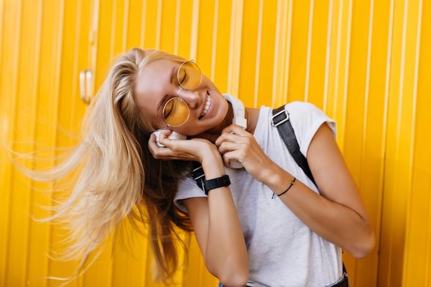 Vrij gebruinde vrouw die in zonnebril favoriete liedje met gesloten ogen op geel luistert