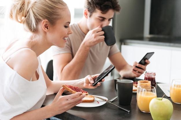 Vrij geconcentreerde liefhebbers die hun smarrtelefoons gebruiken terwijl ze ontbijten in de keuken