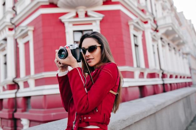 Vrij geconcentreerde vrouwelijke fotograaf tijd buiten doorbrengen