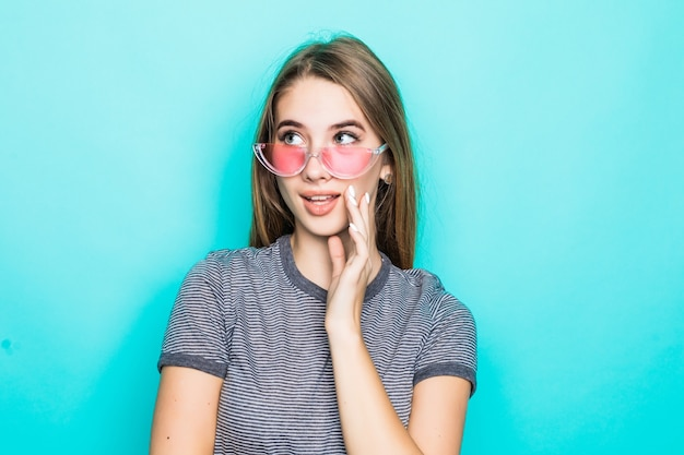 Vrij geil jong model in modet-shirt, hoed en transparante bril die op groene achtergrond wordt geïsoleerd