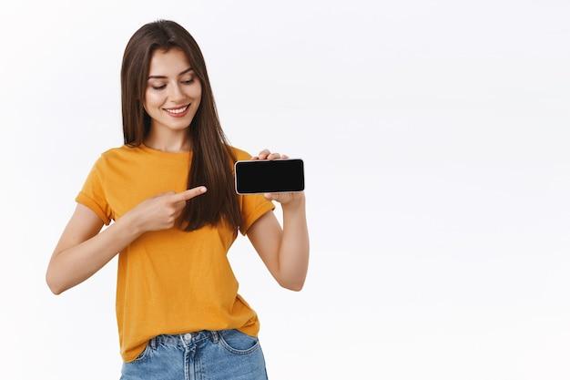 Vrij geïnteresseerde blanke vrouw in geel t-shirt met smartphone horizontaal, wijzend en tevreden kijkend naar mobiel scherm als het tonen van een app voor vriendenwinkelen of opscheppen van foto's van de reis