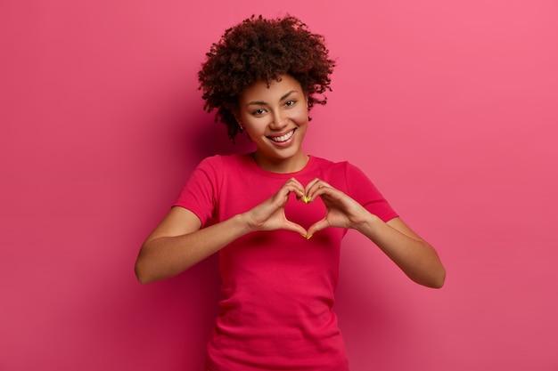 Vrij gekrulde afro-amerikaanse vrouw bekent in liefde, maakt hartgebaar, toont haar ware gevoelens, heeft een blije uitdrukking, draagt een casual rood t-shirt, poseert over de roze muur. relatie concept