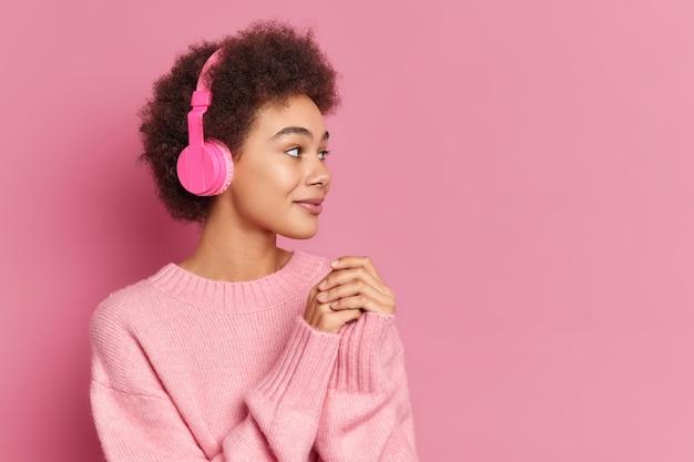 Vrij gekrulde haired etnische vrouw draagt stereo koptelefoon op oren geconcentreerd opzij met belangstelling luistert muziek casual jumper