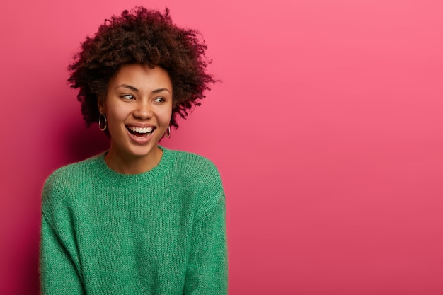 Vrij gekrulde vrouw kijkt opzij met dromerige vrolijke uitdrukking, glimlacht breed, drukt goede emoties uit, draagt groene trui, heeft een aantrekkelijk uiterlijk, geïsoleerd op roze muur met lege ruimte