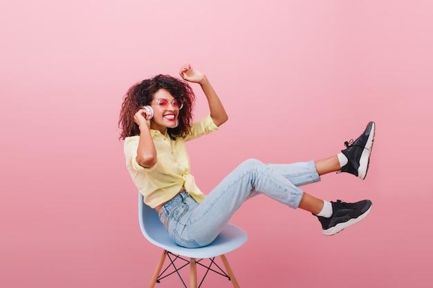 Vrij gekrulde vrouw met bronzen huid poseren in nieuwe zwarte sneakers. fascinerende bruinharige dame in witte sokken chillen in stoel en lachen.