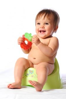 Vrij gelukkig babykind zit op groen potje en houdt bijtring in handen.