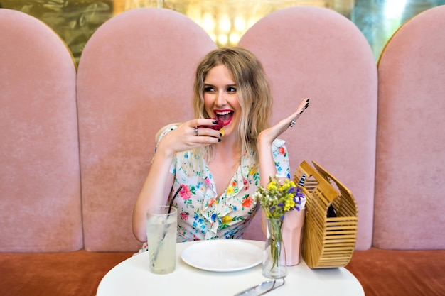 Vrij gelukkig blonde hipster vrouw smakelijke frambozen dessert cake eten, zittend op leuke bakkerij, geniet van haar maaltijd, zoet ontbijt, dieet voeding concept.