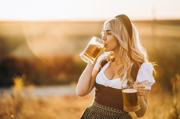 Vrij gelukkig blonde in dirndl, traditionele festival jurk, met twee mokken bier buiten in het veld