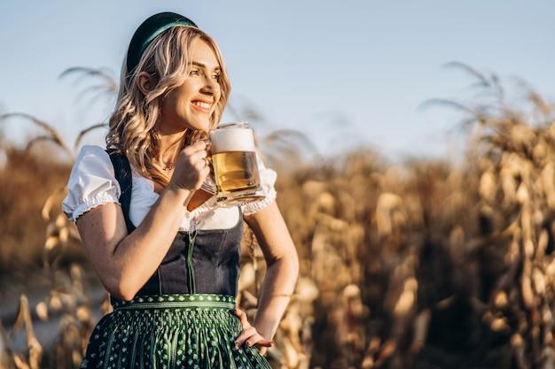 Vrij gelukkig blonde in dirndl, traditionele festival jurk, mok bier buiten in het veld te houden