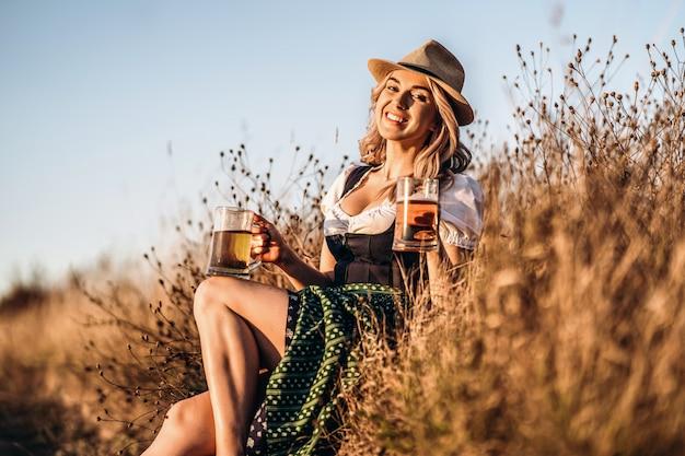 Vrij gelukkig blonde in dirndl, traditionele festival jurk, zittend met twee mokken bier buiten in het veld