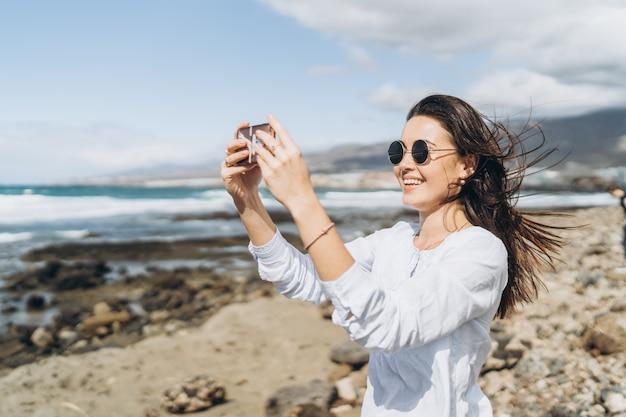 Vrij gelukkig donkerbruin meisje met slimme telefoon op het strand dichtbij oceaan.