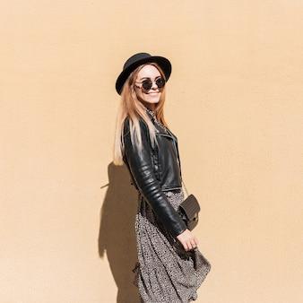 Vrij gelukkig hipstermeisje met een mooie glimlach in modieuze kleding met een leren jas, vintage jurk, hoed en zonnebril loopt in de stad tegen de achtergrond van een gele muur
