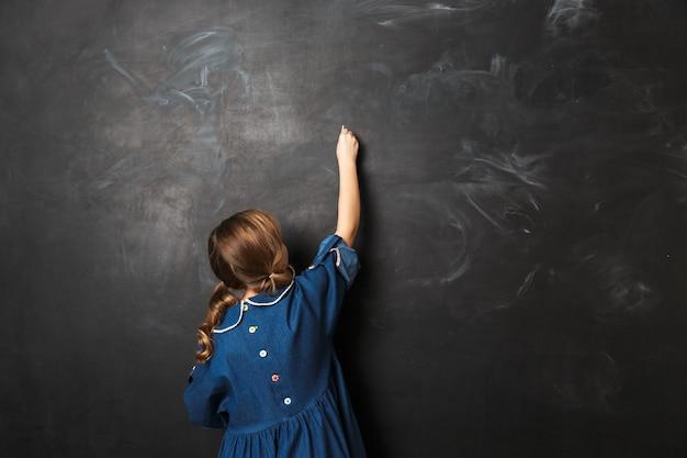 Vrij gelukkig jong schoolmeisje poseren geïsoleerd over schoolbord muur muur.