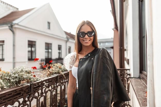 Vrij gelukkig jonge vrouw hipster met een mooie glimlach in stijlvolle kleding in modieuze zonnebril staat op een vintage balkon met bloemen met uitzicht op een stadsstraat. blij schattig meisje mannequin.