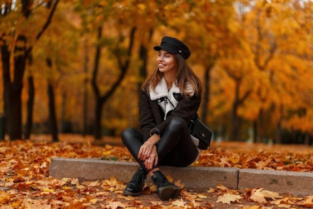 Vrij gelukkig jonge vrouw in een chique hoed in een stijlvol jasje met een tas ontspant in het bos op een achtergrond van gouden bladeren. blij meisje zit in het park. herfstcollectie trendy dameskleding.