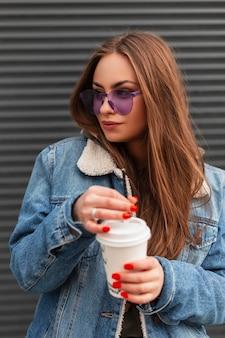 Vrij gelukkig jonge vrouw model in trendy paarse bril in stijlvol spijkerjasje met kopje warme drank poseren in de buurt van een metalen wand buiten. het mooie hipstermeisje met koffie geniet van de lentedag.