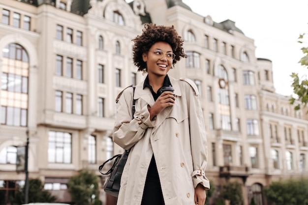 Vrij gelukkige brunette vrouw in trendy beige trenchcoat, zwarte jurk en bril glimlacht, houdt koffiekopje vast en loopt naar buiten