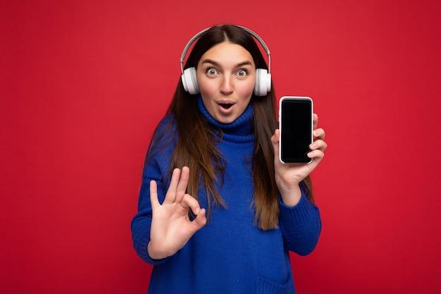 Vrij gelukkige geschokte jonge donkerbruine vrouw die blauwe sweater draagt die over rode achtergrond wordt geïsoleerd