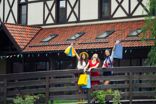 Vrij gelukkige heldere vrouwen vrouwelijke meisjes die in kleurrijke kleding en hoge hielen met het winkelen zakken bij straat na het winkelen lopen