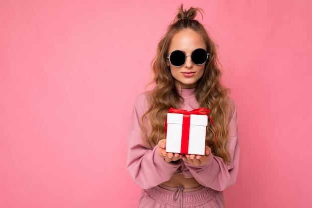 Vrij gelukkige jonge blonde krullende vrouw die over roze muur wordt geïsoleerd als achtergrond die roze sportkleren draagt