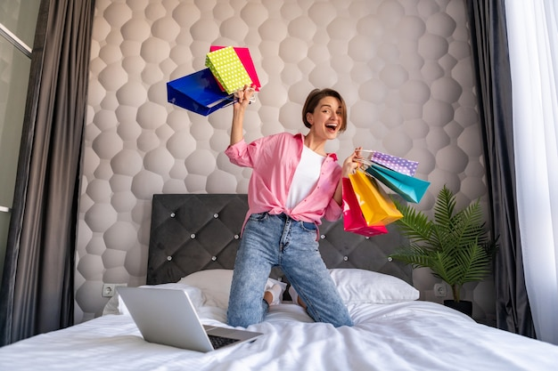 Vrij gelukkige vrouw die plezier heeft in het springen op bed thuis met kleurrijke boodschappentassen