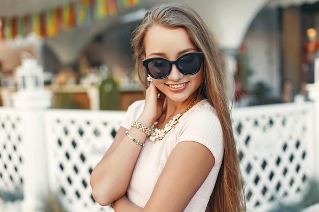 Vrij gelukkige vrouw met een glimlach in zonnebril dichtbij het witte hek
