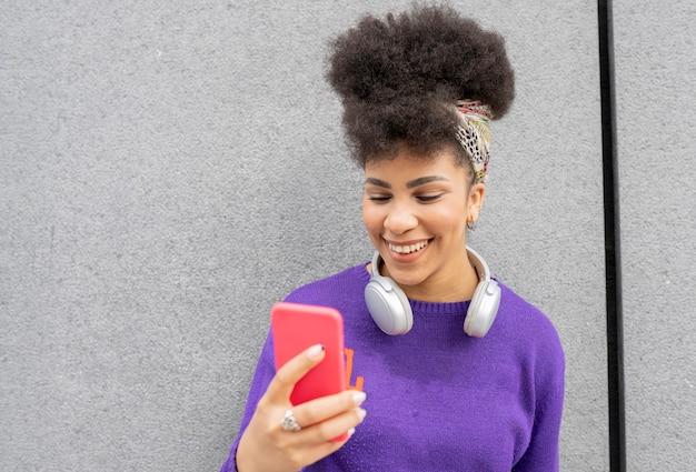Vrij gemengd ras vrouw, gekleed in paarse casual kleding lachend met koptelefoon en smartphone op straat