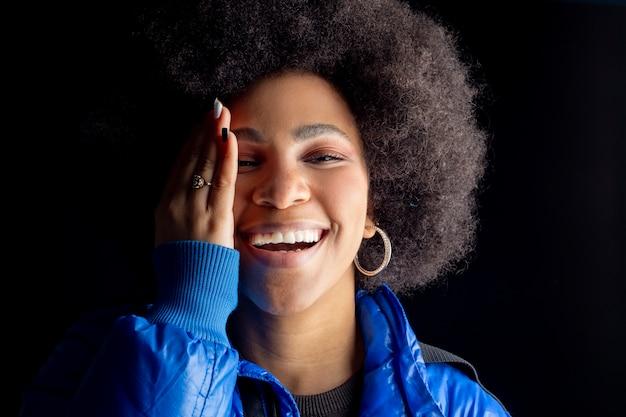 Vrij gemengde afro-vrouw, glimlachend, met stedelijke kleding bedekt half gezicht met haar hand, donker oppervlak