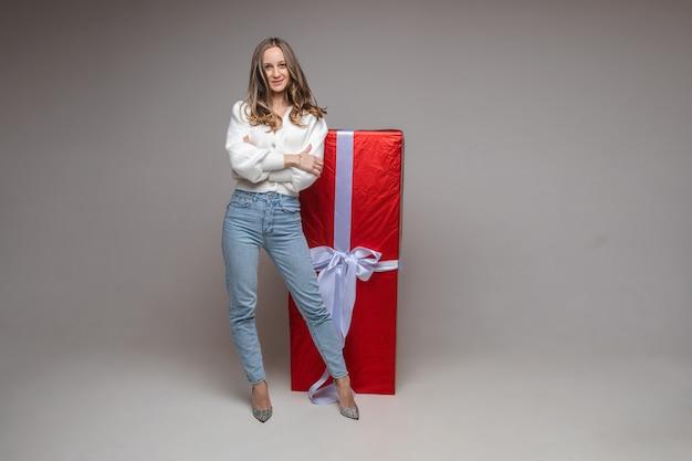 Vrij geschikte jonge vrouw met grote rode gift op grijze studioachtergrond met exemplaarruimte voor vakantiereclame