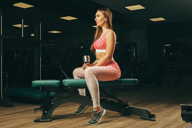 Vrij geschikte vrouw die oefeningen in een gymnastiek doet