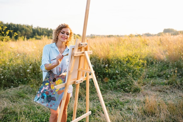 Vrij getalenteerde vrouwelijke schilder die op ezel schildert, kleurrijke schetsen maakt, marien landschap creëert. mooie vrouwelijke kunstenaar schilderen met aquarelverf. creativiteit en verbeelding concept.