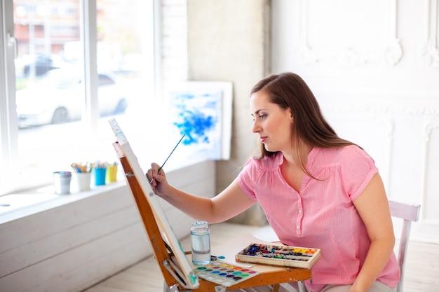 Vrij getalenteerde vrouwelijke schilder die op schildersezel schildert