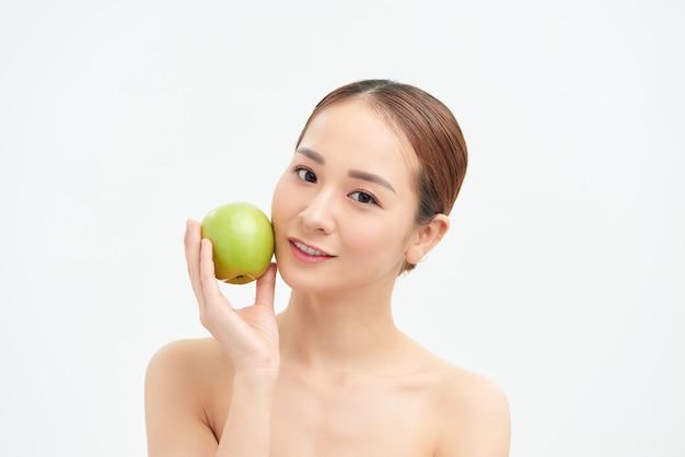 Vrij gezonde jonge vrouw die met een groene appel glimlacht